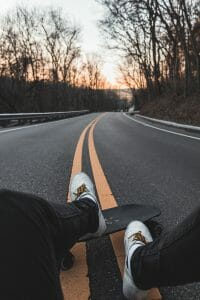 Sitting next to a longboard on the road before going downhill